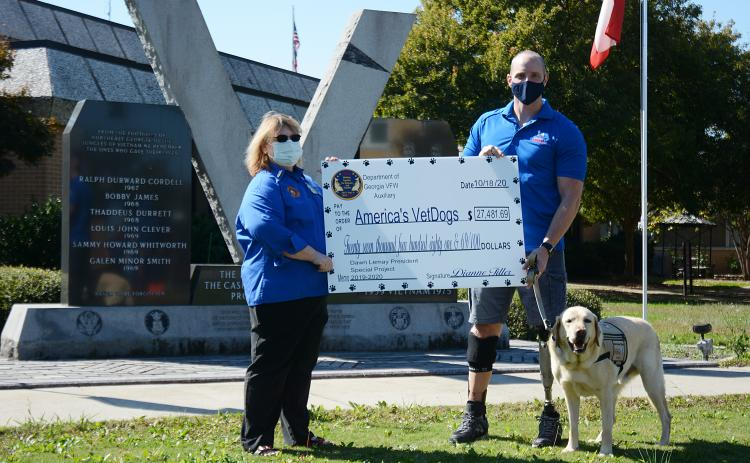 Sunshot by Michael Hall - Dawn Lemay, a Hartwell resident and state president of the Veterans of Foreign Wars Auxiliary, presents a check for $27,481.69 to Joe Worley, of America's VetDogs, and his service dog Galaxie recently at the veterans memorial on the square at the Hart County Courthouse.