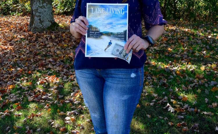 Photo by Kimberly Brown - Heather Conner, of Clayton, holds a copy of the cover of Lake Living Magazine and her $100 in prize money she won in a photo contest for the cover shot.