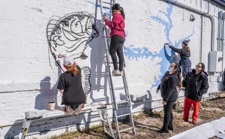 Nora Winkler, from left, Alondra Arevalo, on the ladder, and Katie Eidson, right paint a mural on the rear exterior wall of Little Japan on Depot Street in downtown Hartwell recently as restaurant owners Treena and Tommy Nguyen look on.