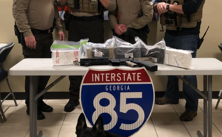 "Capt. Josh Fowler, deputy Matt Sparrow, deputy Brian Anderson, Inv. Michael Davis and K-9 unit ""Chuck"" pose for a photo with more than 11 pounds of cocaine and an AR-15 seized from a charter bus traveling on Interstate 85 on Friday."