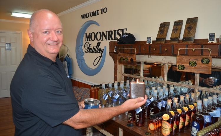 Moonrise DIstillery owner Doug Nassaur shows some of the many bourbon-related products offered for sale at the Clayton distillery.